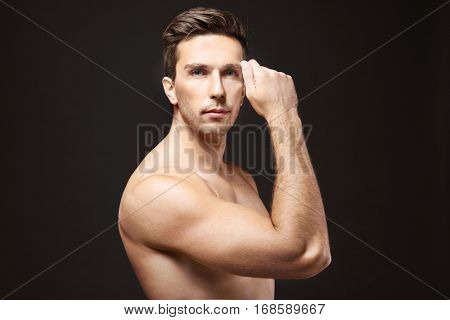 Young man touching his face on black background