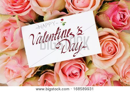 bouquet of pink roses with blank greeting card with happy valentines day greeting