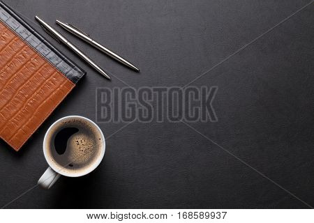 Office leather desk table with notepad, coffee, pen and pencil. Top view with copy space
