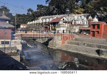KATHMANDU NEPAL - NOV 21 2013 : Hindu cremation rituals at the banks of Bagmati river at Pashupatinath Temple complex in Kathmandu