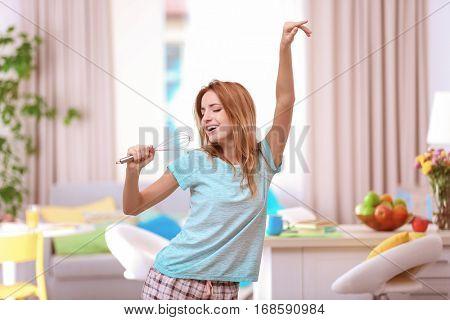 Beautiful young woman dancing at home