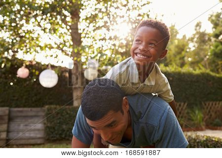 Young black boy playing on his dadâ??s back in a garden