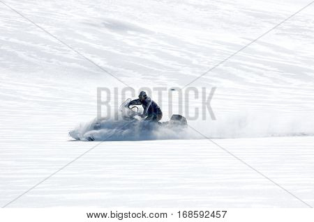 man riding on a snowmobile in a sunny day