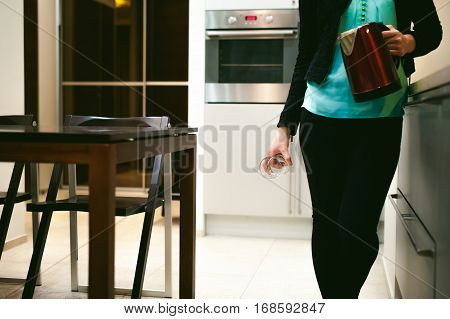 Blonde Woman In The Kitchen Holding A Glass Beaker, Pour The Water From The Kettle To Quench Their T
