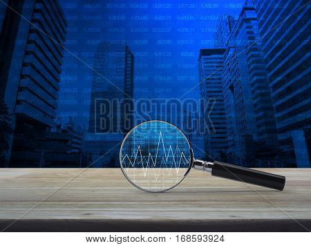 Magnifying glass with graph on wooden table over number and modern office city tower Business analyzing concept
