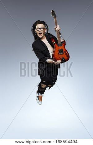 Entertainment and musical concept. Excited rock musician is jumping with his electrical guitar. Full length studio shot.