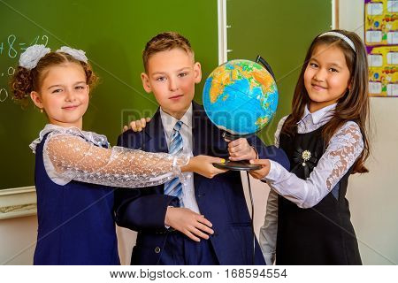 Educational concept. Three happy students standing together with a globe by a schoolboard.