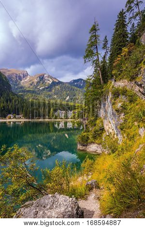 Italy, lake Lago di Braies. The concept of walking and eco-tourism. Emerald expanse of water reflects the surrounding forest and mountains