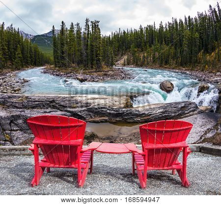 Two red deckchairs stand on the shore of the river. Jasper National Park, Canada. Small island in the middle of the river. The concept of extreme and ecological tourism