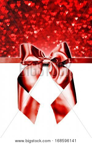 Red gift ribbon bow and heart bokeh isolated on white background