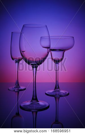 Glasses for drinks on a bar counter a color neon background