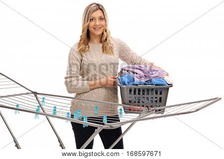 Happy girl holding a laundry basket full of clothes behind a clothing rack dryer isolated on white background