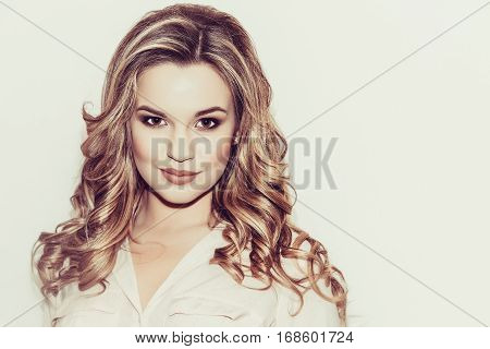 Blonde with long hair and laid Evening make-up on a light background