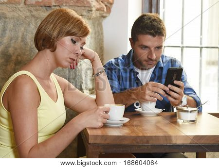 young American couple at coffee shop with internet and mobile phone addict man ignoring bored sad and frustrated woman girlfriend or wife in relationship problem and addiction concept