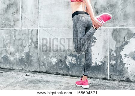 Fitness sport woman in fashion sportswear doing yoga fitness exercise in the city street over gray concrete background. Outdoor sports clothing and shoes, urban style. poster