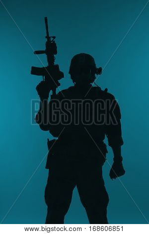 United states Marine Corps special operations command Marsoc raider with weapon. Silhouette of of Marine Special Operator blue background