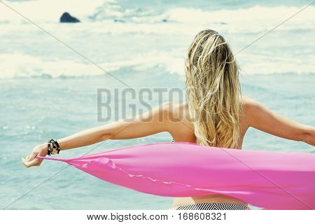 Blond young woman back with open arms, taking a silk cloth watching the sea. A young woman holds a lightweight silk cloth in the wind.