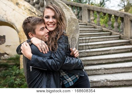 Portrait of beautiful lovers, men and women who embrace. The old dilapidated building and a large spiral staircase on the background. Space for text