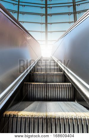 Modern escalator with window at the background.