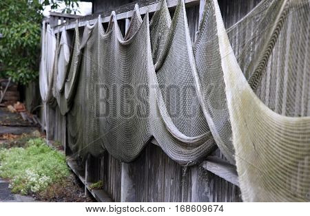 Fishing nets drying on the fence .