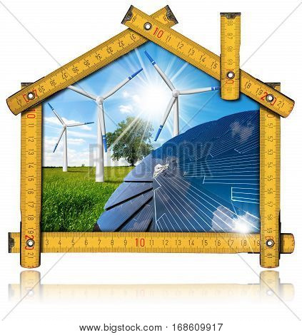 Wooden ruler in the shape of ecologic house with a solar panel and wind turbines in countryside with blue sky clouds and sun rays. Green energy concept