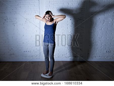 young fit slim woman or teen girl checking body weight on scale with big shadow light sad desperate and frustrated obsessed with overweight in anorexia and bulimia nutrition disorder