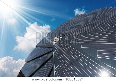 Solar panel in the shape of a flower on a blue sky with clouds and sun rays