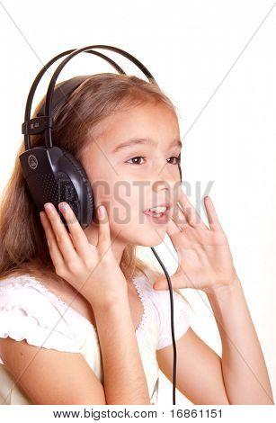 Cute little girl listening music in headphones