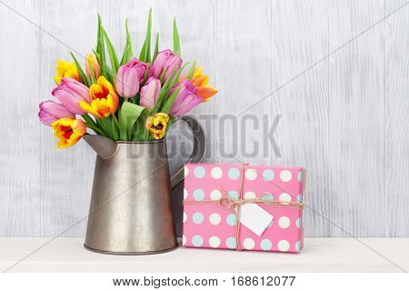 Fresh colorful tulip flowers bouquet and gift box on shelf in front of wooden wall