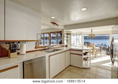 Compact kitchen with white cabinetry accented with wood pulls alongside white quartz counters modern stainless steel appliances and beige tile floor. Northwest USA poster