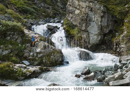 SILVRETTA - AUGUST 13: A young woman in hiking clothes watching a mountain waterfall in the Silvretta region Austriay on August 13 2015.