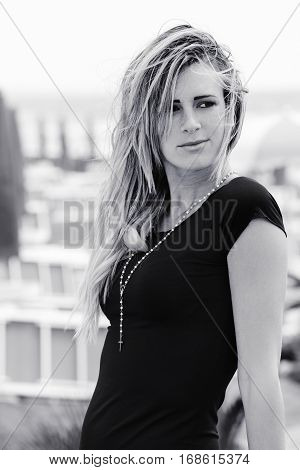 Blonde girl portrait in black and white. Outdoor, long straight hair. A sweet and charming girl woman with black dress and necklace with crucifix.