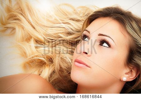 Female beauty. Young blond hair girl face. Close portrait of a young blonde girl woman. Hair flat on the floor.