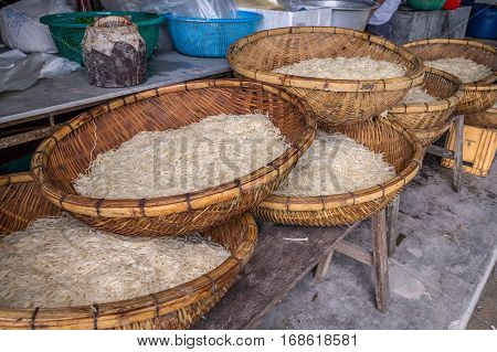 Asian dried gelatin noodles food in wooden baskets on wooden bench in a rural kitchen