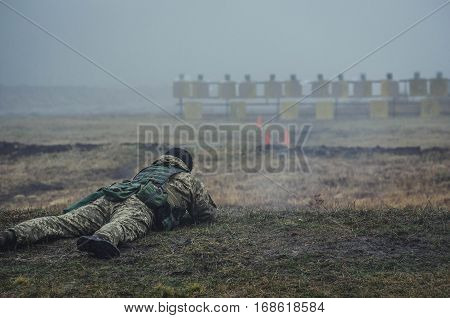 Ukranian soldier is shooting in prone position during military training in fog landscape