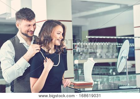 Young brunet man choosing present and holding on neck his pretty wife, white pearl necklace. Happy couple of buyers looking at mirror and smiling each other. Luxury jewelry store.