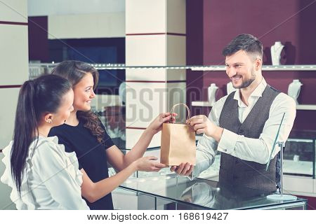 Two pretty women buying jewelry in mall. Jeweler seller and two girls holding little paper bag by arms, looking and smiling to each other. Couple of girlfriend buying present in jewelry store.