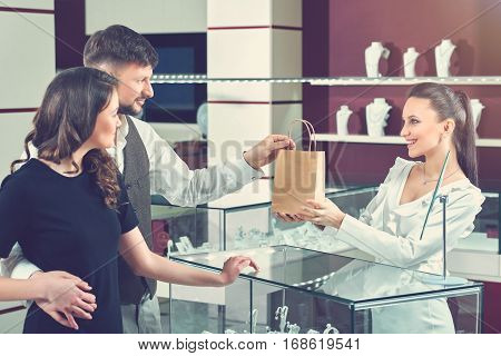 Side view of happy couple of boyfriend and girlfriend with wavy hair buying jewelry in luxury store. Seller giving for couple little paper bag with purchase, looking and smiling to buyers.