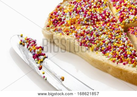 Fairy bread with butter knife, side view.  Traditional Australian children's party food, hundreds and thousands candy sprinkles on white bread.