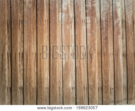 Lath arranged in a vertical manner with nails hold the wood in the sun throughout the wood.