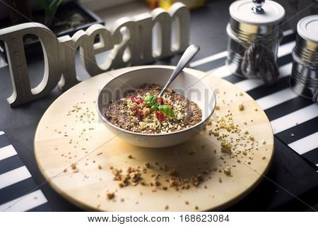 Chocolatiers breakfast   with oatmeal, puffed rice, cereals , dried strawberries and  tea prepared in a white bowl. Big inscription Dream above.