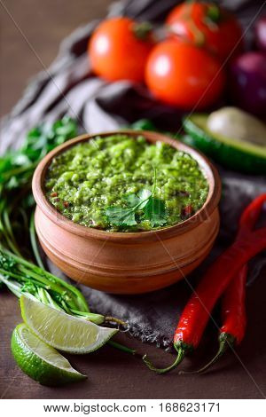 Traditional mexican dip or sauce guacamole in a rustic bowl front view