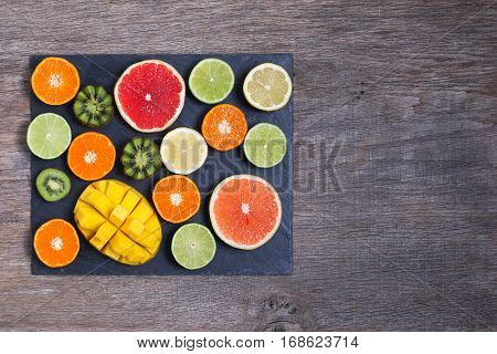 Raw fruit rich in vitamin C on the black slate platter: oranges grapefruits lemons limes kiwis slices, top view, copy space for text