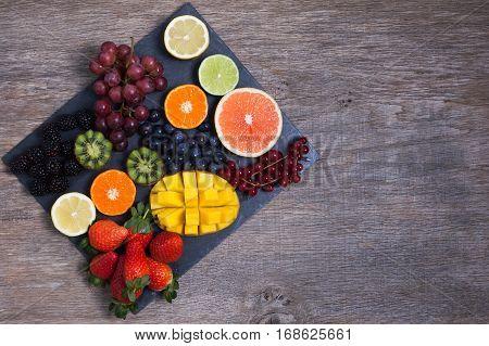 Raw fruit and berries platter mango kiwis strawberries blueberries blackberries red currants grapes top view, copy space