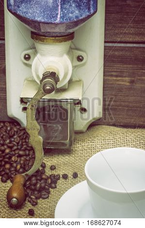 Closeup view of the vintage photo of the empty white cup of coffee and manual coffee grinder standing on the sackcloth. Around it are scattered coffee beans. Vertically.