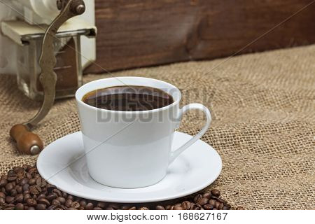 The vintage photo of the cup of coffee standing on the sackcloth. Around it are scattered coffee beans. The part of manual coffee grinder is standing in the background. Free place for your text is in the right side of the photo.