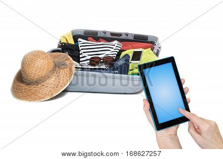 Female is holding tablet and touching the blank touchscreen. Suitcase with glasses smart phone dress and straw hat is ready to travel. All is in the white background.