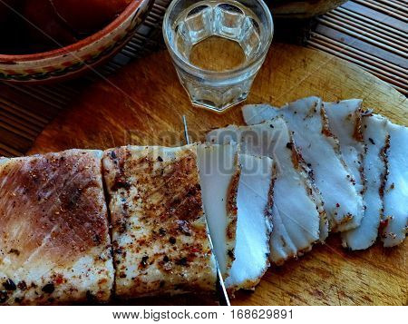 Homemade lard with condiments. Glass of vodka, pickled tomatoes. Natural food, appetizer. Closeup. Traditional Dishes of Russian Cuisine