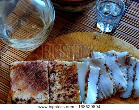 Homemade lard with condiments. Carafe and a glass of vodka. Natural food, appetizer. Closeup. Traditional Dishes of Russian Cuisine