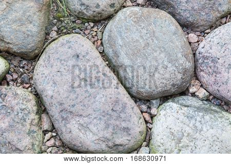 Old road paved of stones. Cobble background